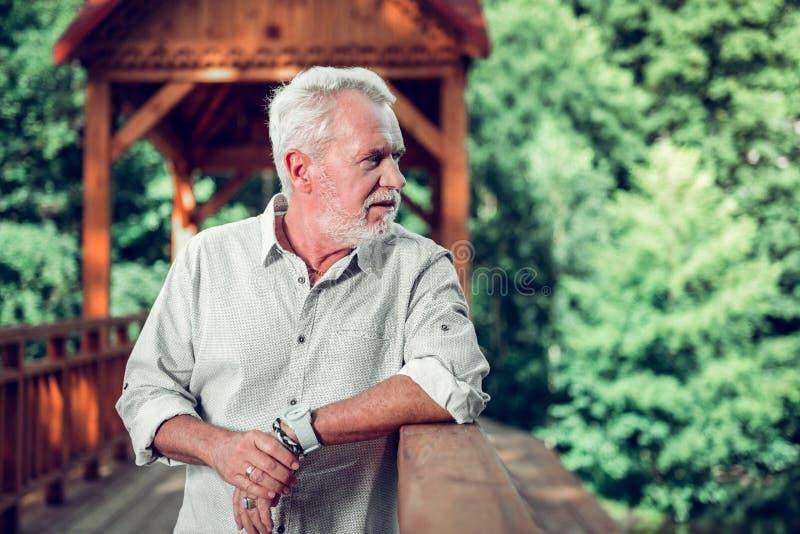 Портрет стороны человека полагаясь на деревянном мосте стоковое изображение