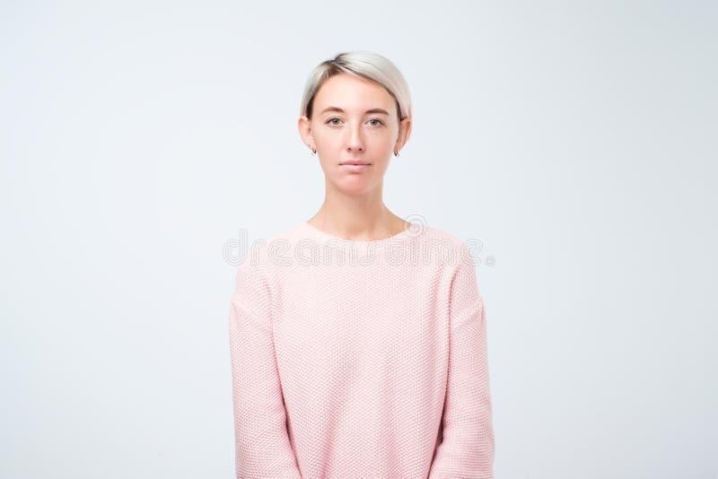 Портрет стоять стильной молодой милой женщины усмехаясь в розовом свитере на белой предпосылке студии стоковое изображение