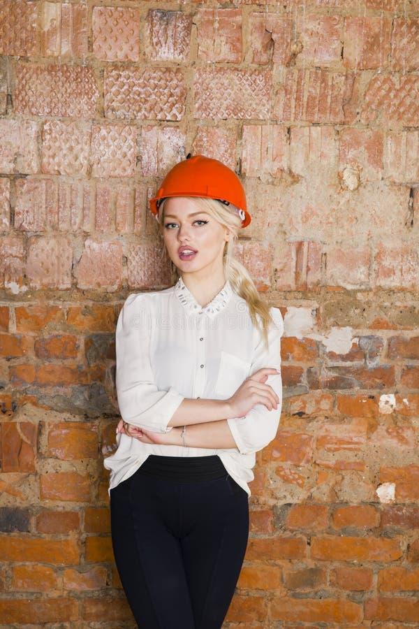 Портрет студента архитектора или художник с светокопиями защищают носить шлема Предпосылка красного цвета кирпича стоковое изображение rf