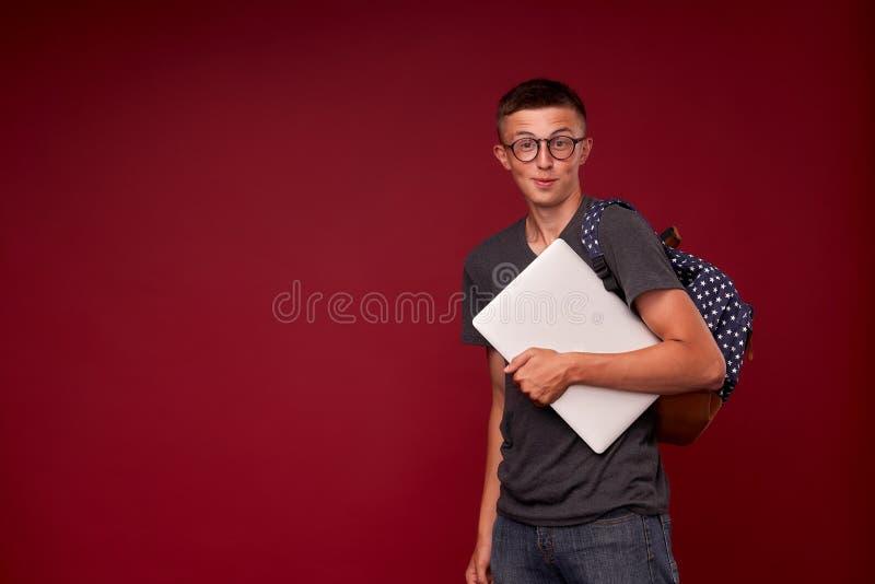 Портрет студента мальчика с рюкзаком и ноутбуком в его руках усмехаясь на красной предпосылке смешной положительный подросток мак стоковая фотография rf