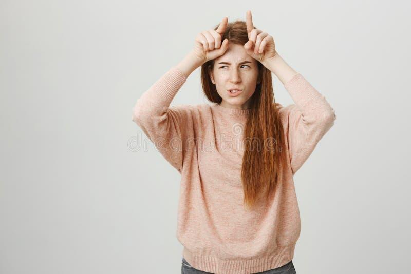 Портрет студента привлекательного redhead европейского держа указательные пальцы на лбе любит рожки дьявола с злим выражением стоковое фото rf