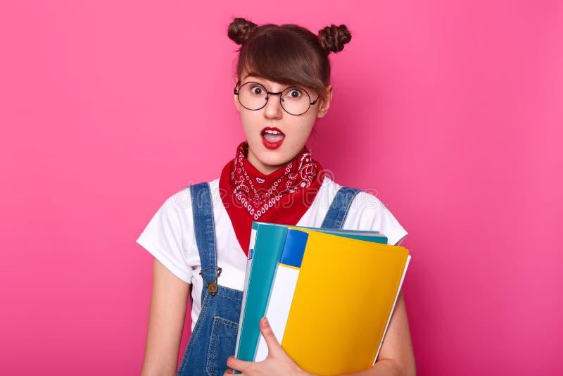 Портрет студента с 2 пуками, носит белую футболку, прозодежды джинсовой ткани, красный bandana и округленные стекла, держа colouu стоковое изображение