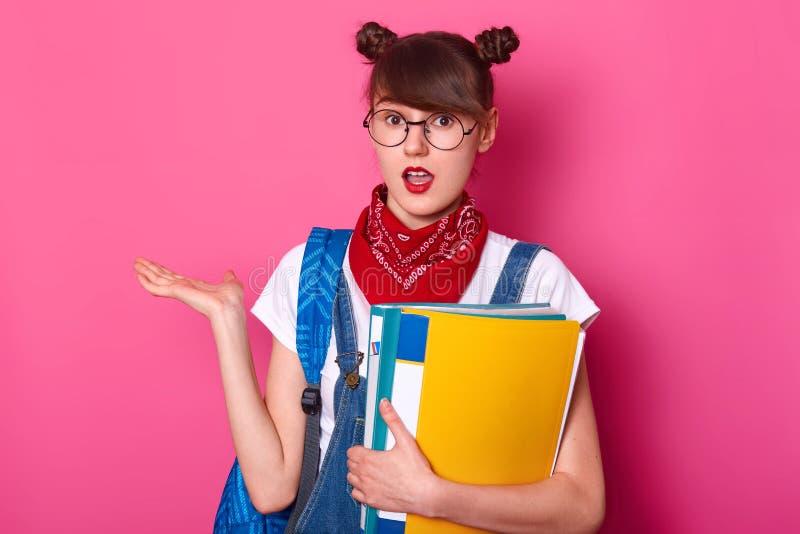 Портрет студента с 2 пуками, носит футболку, прозодежды, bandana, держит папку бумаги, принимает ладонь в сторону, удивлял стоковые фотографии rf