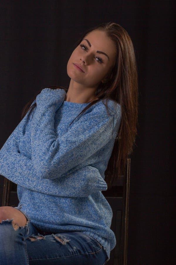 Портрет студии красивой молодой женщины нося голубой свитер представляя обнимающ стоковая фотография rf