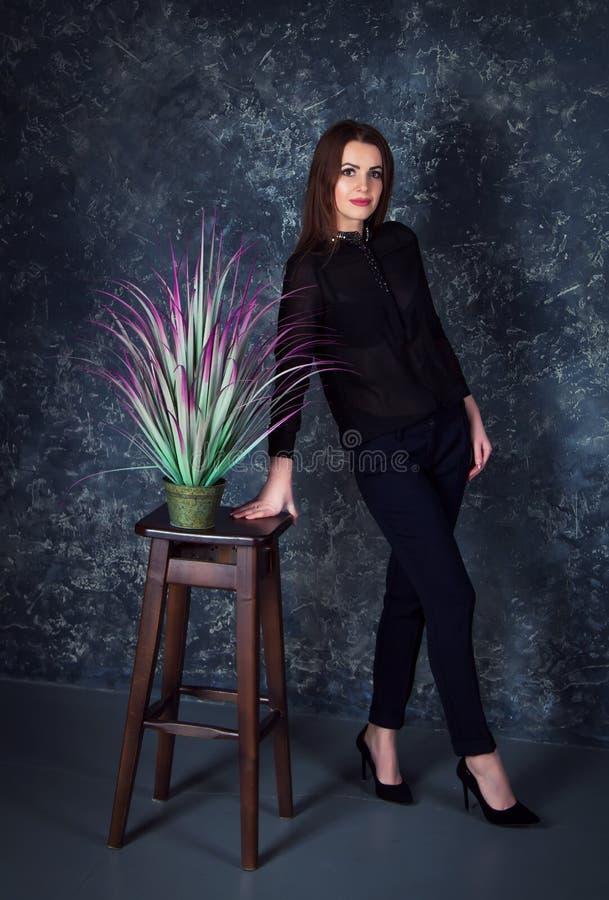 Портрет студии красивой молодой усмехаясь женщины нося голубые джинсы и куртку джинсовой ткани стоковое фото rf
