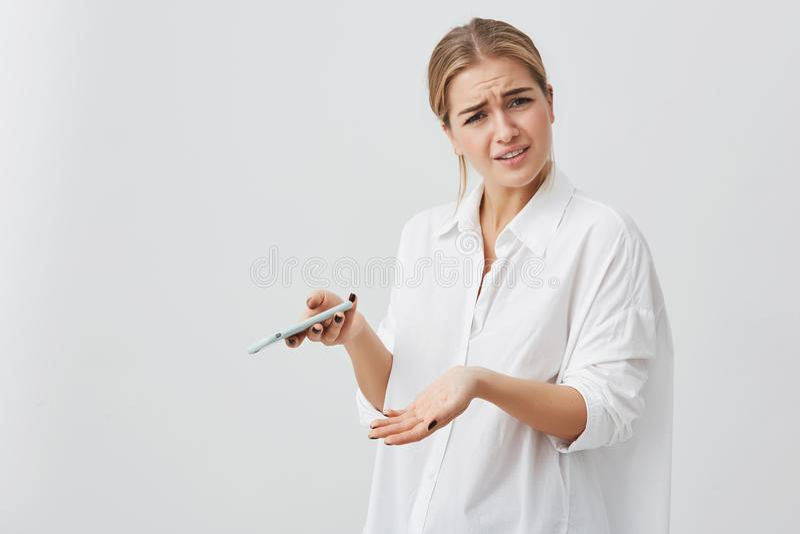Портрет студии озадаченной или тревоженой милой девушки с белокурыми волосами хмурясь ее сторона смотря телефон видя плохую новос стоковые фото