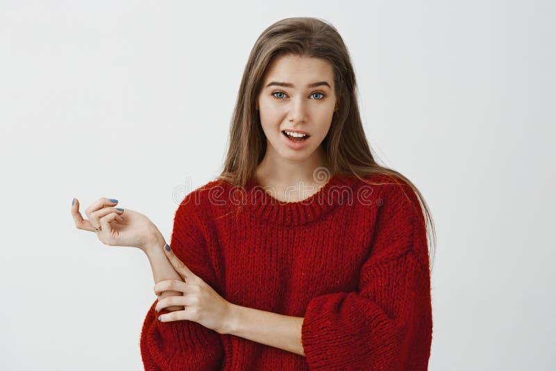Портрет студии сомнительной не поддавшийся эмоциям милой подруги в ультрамодном свободном свитере, показывать с головой и поднима стоковая фотография