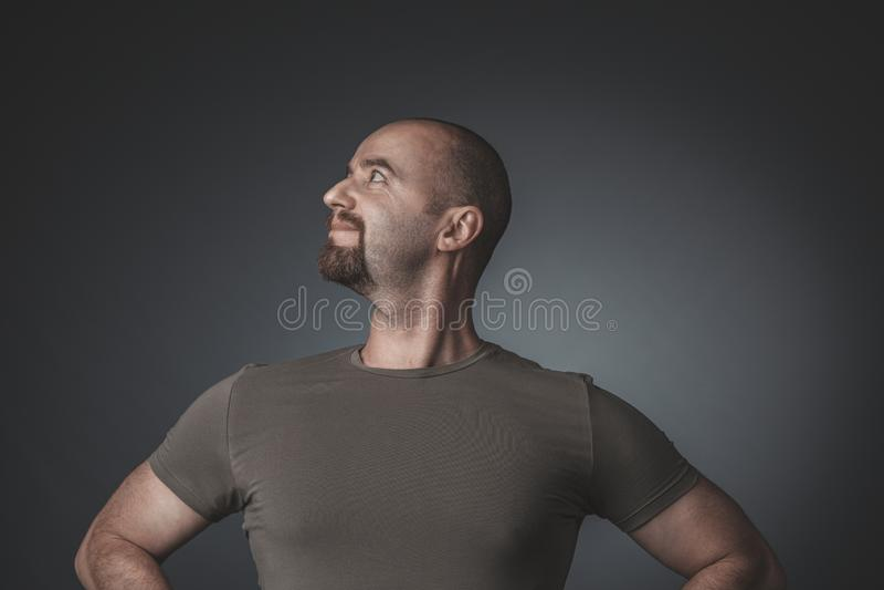 Портрет студии человека с удовлетворенным и гордым выражением, взглядом со стороны стоковая фотография