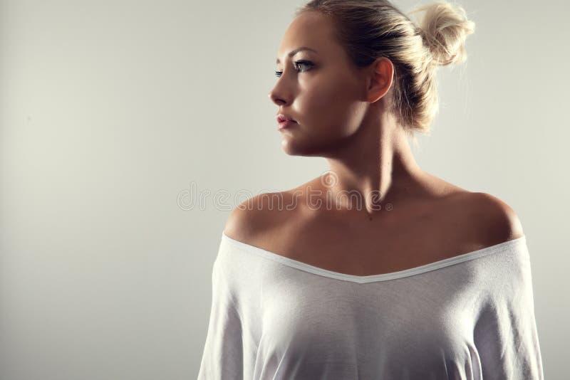 Портрет студии шикарной женщины со светлыми волосами и белой футболкой стоковое фото