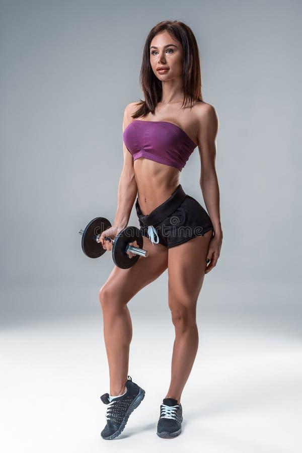 Портрет студии sporty молодой женщины представляя с гантелью против серой предпосылки стоковые изображения rf