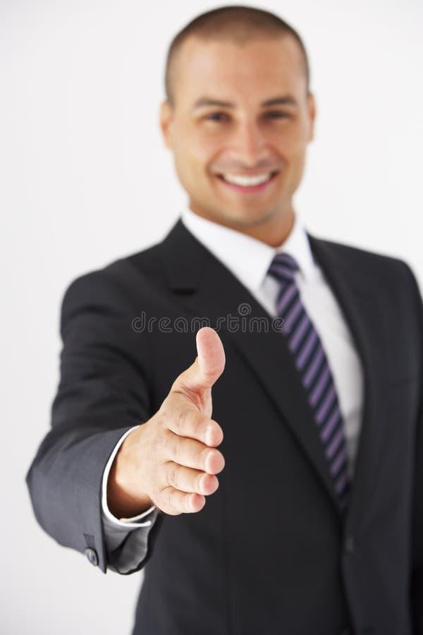 Портрет студии бизнесмена достигая вне для того чтобы трясти руки стоковое фото rf