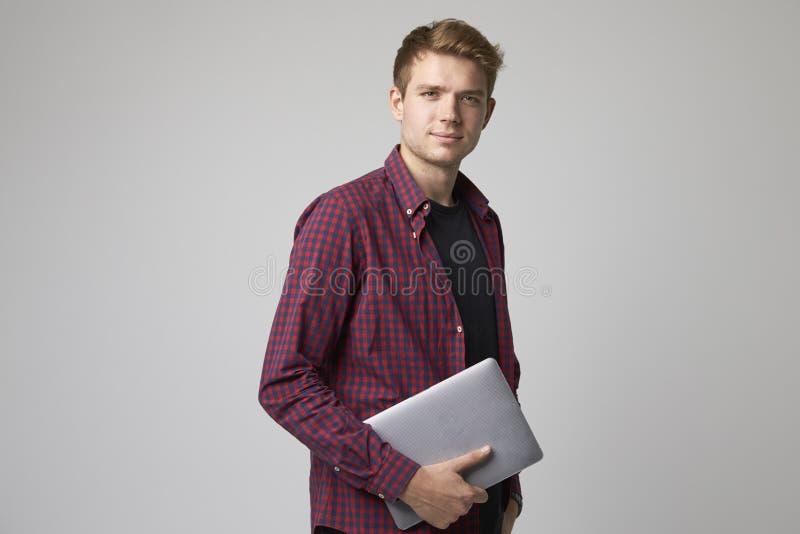 Портрет студии вскользь одетого бизнесмена с компьтер-книжкой стоковое фото