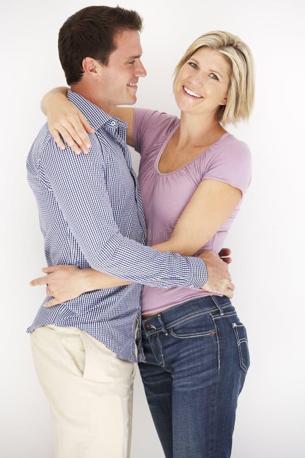 Портрет студии романтичных пар обнимая против белого Backg стоковые фотографии rf