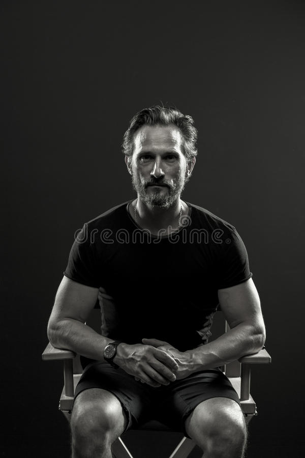 Портрет студии среднего постаретого человека сидя на стуле стоковые фото