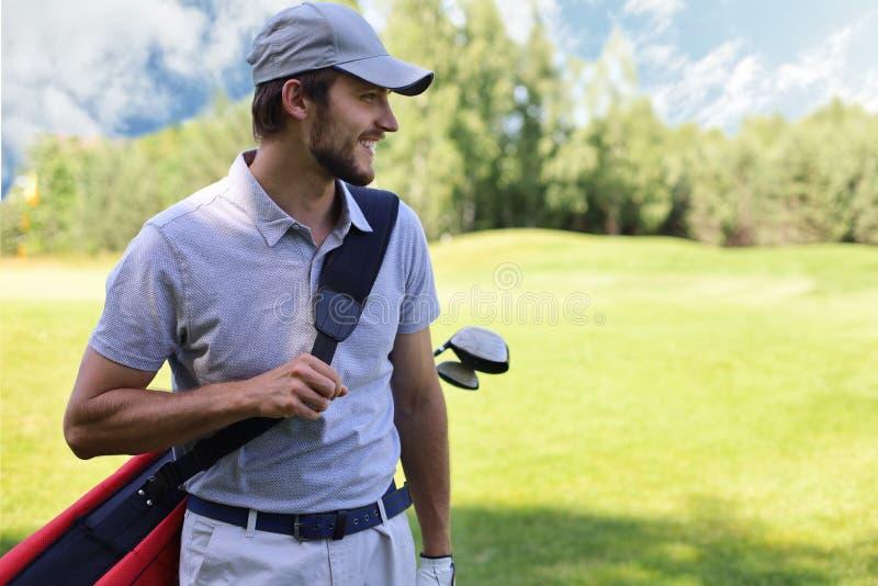 Портрет сумки нося гольфа мужского игрока в гольф пока идущ зеленой травой гольф-клуба стоковые фотографии rf
