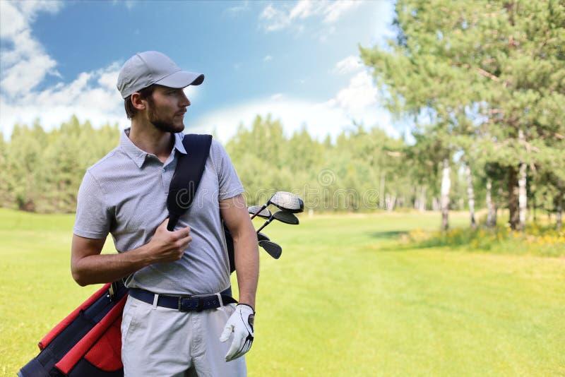 Портрет сумки нося гольфа мужского игрока в гольф пока идущ зеленой травой гольф-клуба стоковые изображения rf