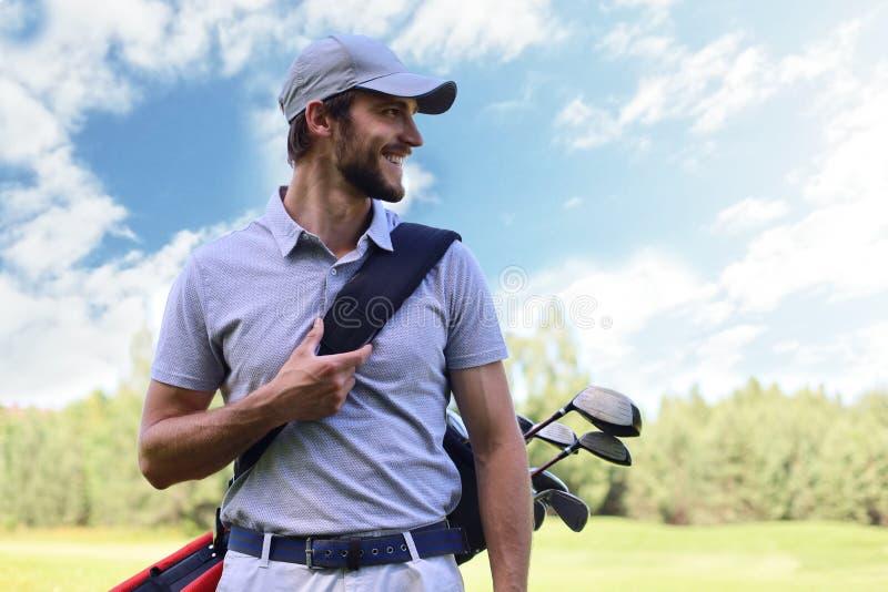 Портрет сумки нося гольфа мужского игрока в гольф пока идущ зеленой травой гольф-клуба стоковые изображения