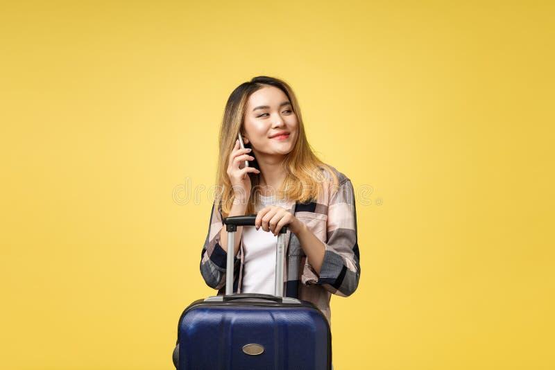 Портрет счастливого азиатского женского путешественника с чемоданом и смотреть мобильный телефон против изолированной желтой пред стоковые изображения rf