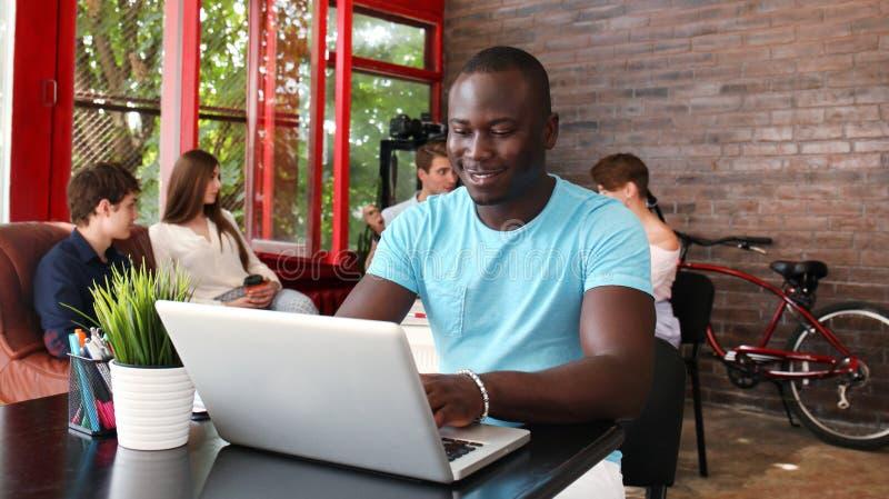 Портрет счастливого Афро-американского предпринимателя показывая компьютер в офисе стоковые изображения rf
