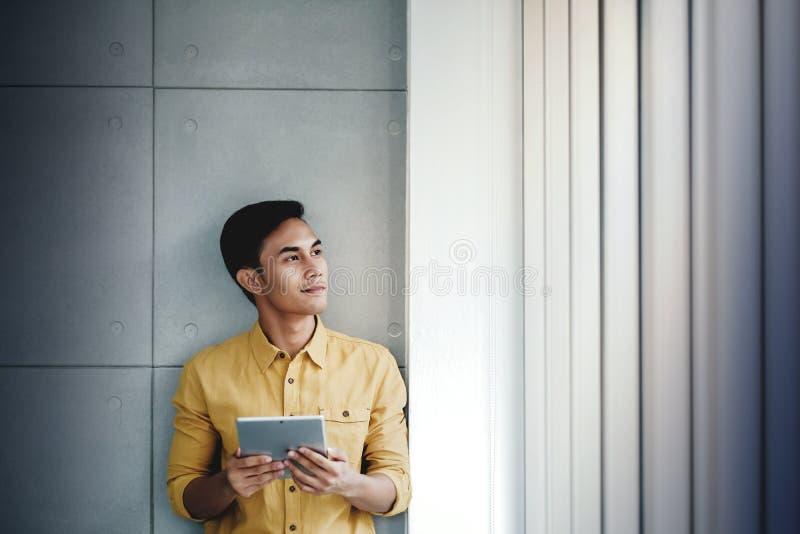 Портрет счастливого бизнесмена готовя окно в офисе Используя планшет цифров Смотреть прочь и усмехаться стоковое изображение rf