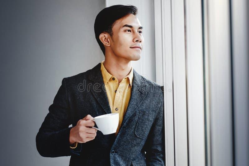 Портрет счастливого бизнесмена готовя окно в офисе Смотреть отсутствующий и усмехаться Мечтать для успеха стоковые изображения rf