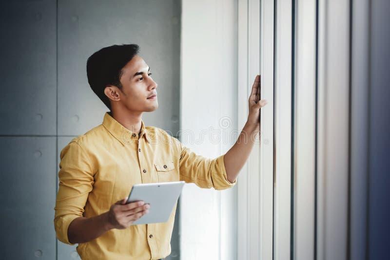 Портрет счастливого бизнесмена готовя окно в офисе цифровая таблетка используя Смотреть отсутствующий и усмехаться стоковое изображение rf