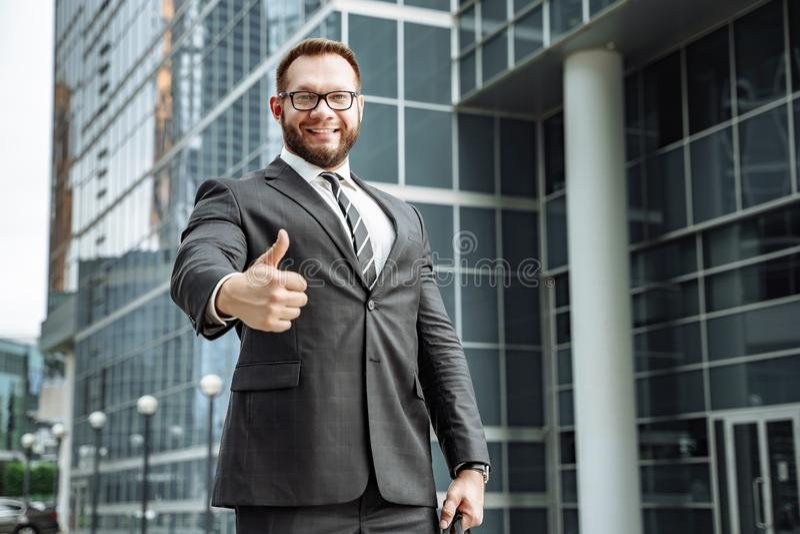 Портрет счастливого бизнесмена показывая его большой палец руки вверх на предпосылке делового центра стоковая фотография