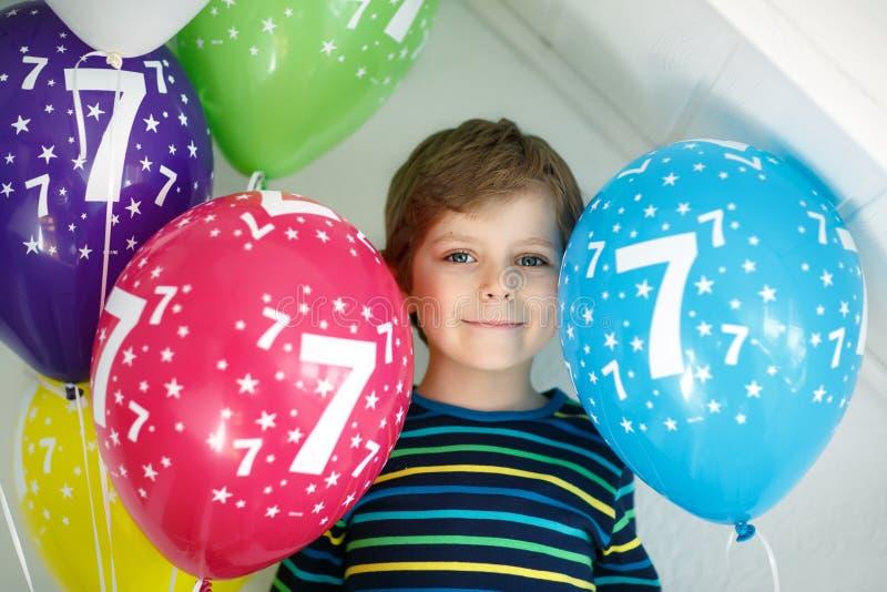 Портрет счастливого мальчика ребенк с пуком на красочных воздушных шарах на дне рождения 7 Усмехаясь ребенок школьного возраста и стоковое фото rf