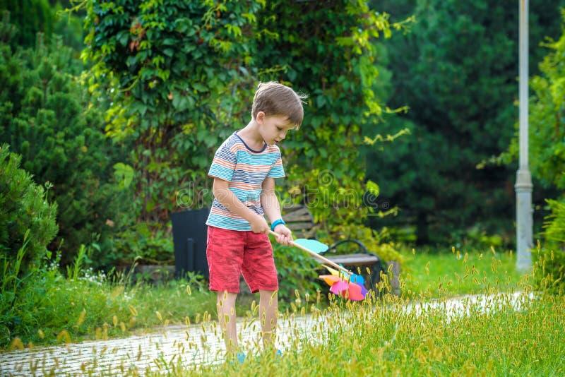 Портрет счастливого милого мальчика держа pinwheel на парке владение ребенк в игре руки с ветрянкой мальчик усмехаясь весной или стоковые изображения