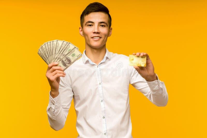 Портрет счастливого молодого азиата, держащего кредитку и деньги в руках, улыбающегося и смотрящего на камеру стоковое фото