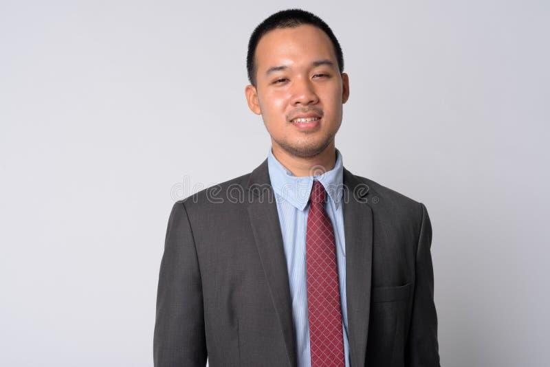 Портрет счастливого молодого азиатского бизнесмена в усмехаться костюма стоковая фотография