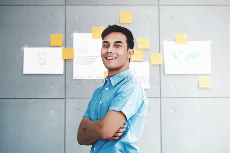 Портрет счастливого молодого азиатского бизнесмена пересек оружия и усмехаться в конференц-зале офиса стоковое фото rf