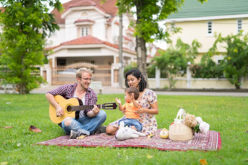 Портрет счастливого мульти-этнического выпуска облигаций семьи вместе с музыкой outdoors стоковые изображения rf