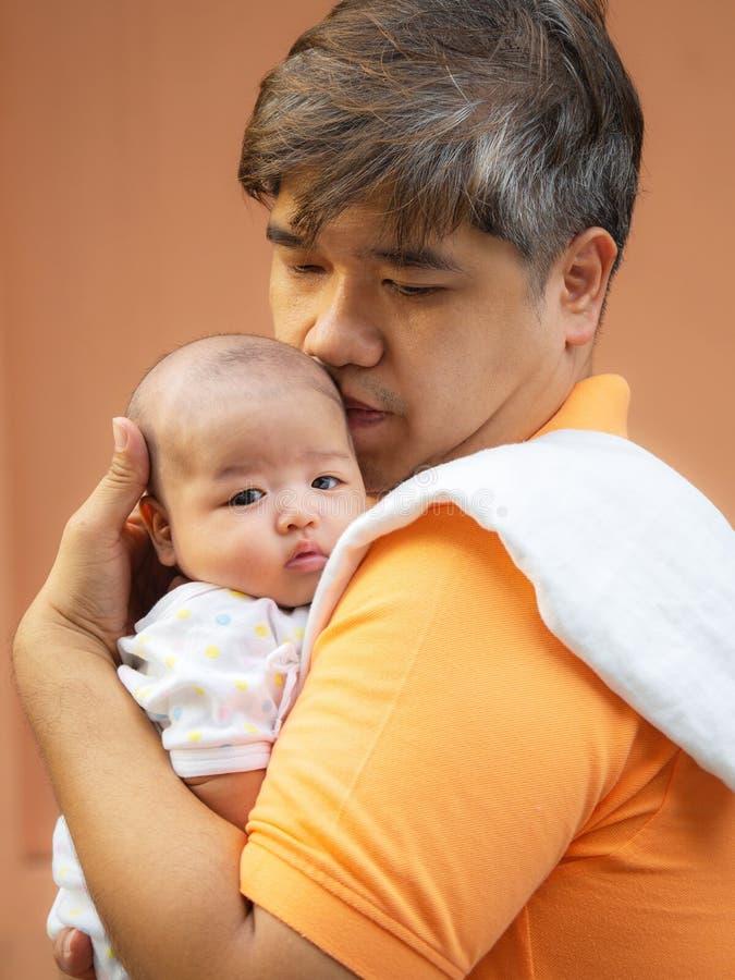 Портрет счастливого отца Азии держа его newborn сладостного младенца одел в белых одеждах Отец обнимая его младенца с влюбленност стоковая фотография