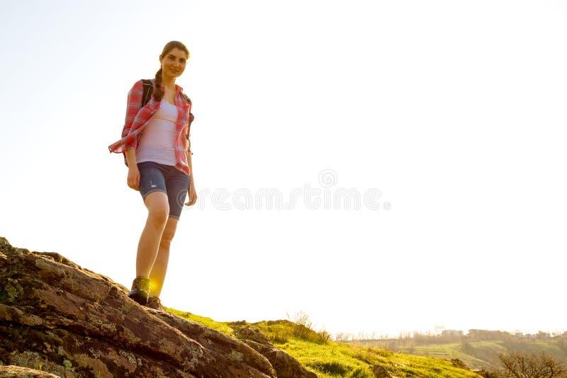 Портрет счастливого путешественника женщины при рюкзак стоя на утесе на солнечном вечере Концепция перемещения и приключения стоковое фото rf