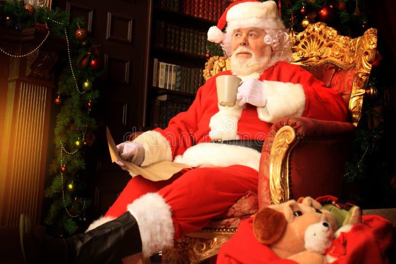 Портрет счастливого Санта Клауса сидя на его комнате дома около рождественской елки и читая письмо или список целей рождества стоковые фото