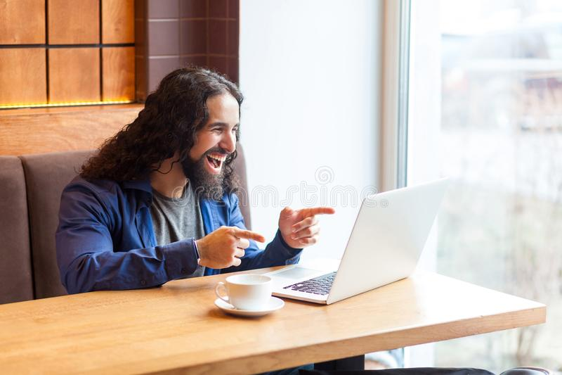 Портрет счастливого удивленного красивого молодого взрослого фрилансера человека в непринужденном стиле сидя в кафе и наблюдая см стоковая фотография rf