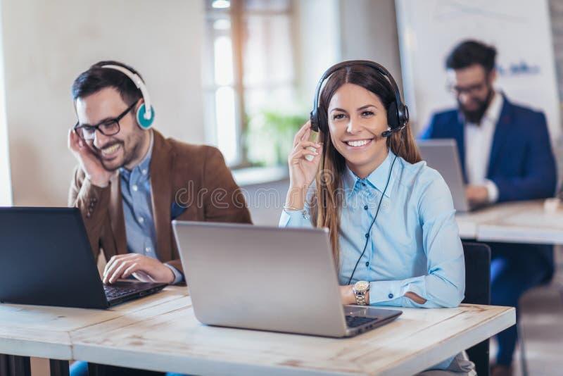 Портрет счастливого усмехаясь женского оператора телефона работы с клиентом стоковое фото