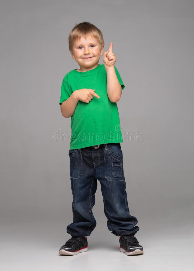 Портрет счастливого усмехаясь мальчика в зеленых футболке и джинсах Привлекательный ребенк в студии стоковые изображения rf