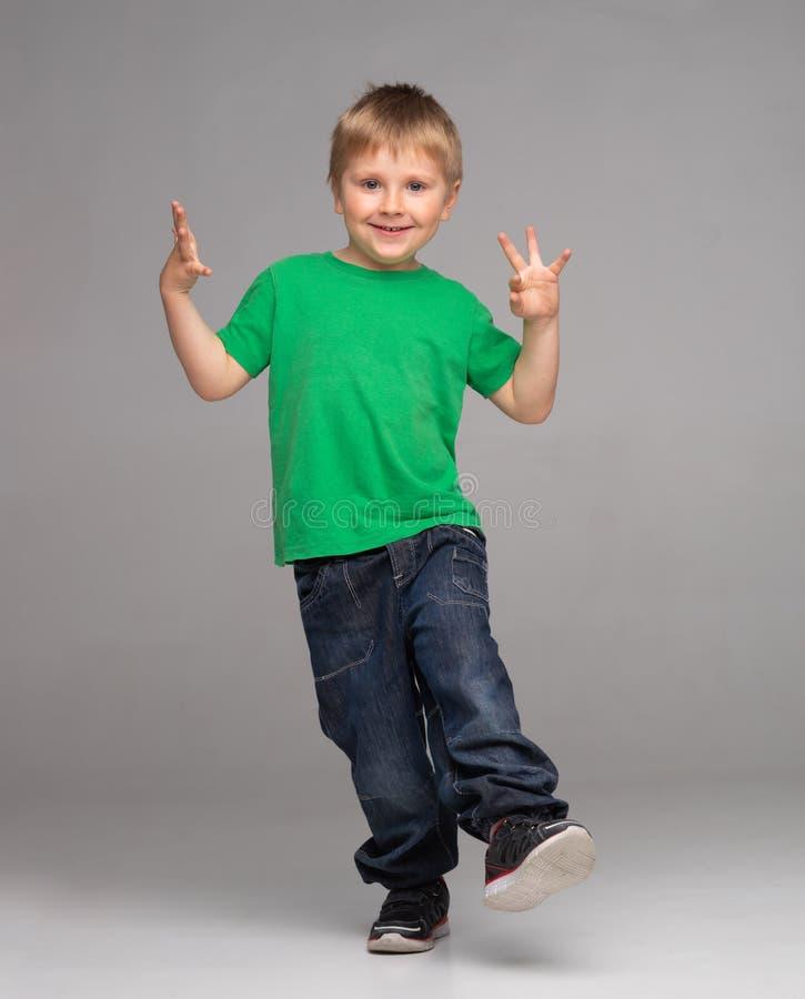 Портрет счастливого усмехаясь мальчика в зеленых футболке и джинсах Привлекательный ребенк в студии стоковые фото