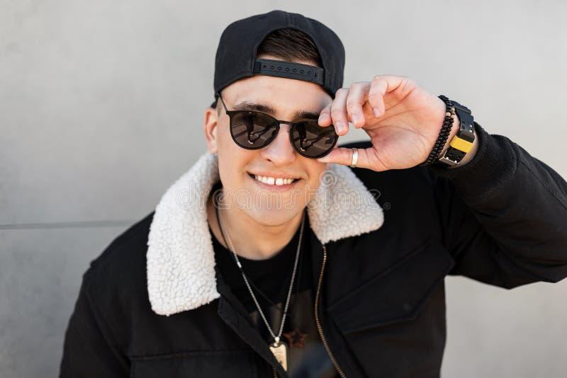 Портрет счастливого хипстера молодого человека с положительной улыбкой в темных солнечных очках в черной стильной куртке в модной стоковая фотография rf