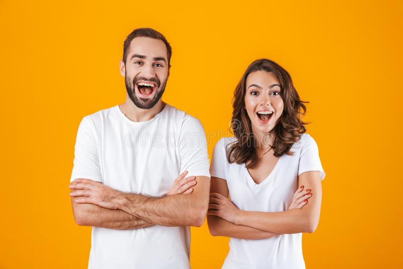 Портрет счастливого человека и женщины людей в основной одежде усмехаясь, пока стоящ совместно изолированный над желтой предпосыл стоковое изображение rf