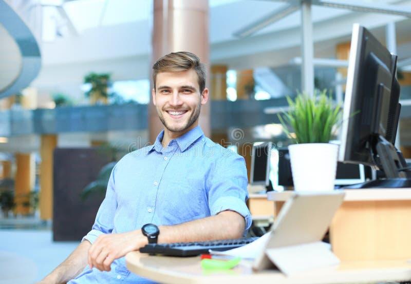 Портрет счастливого человека сидя на столе офиса, смотрящ камеру, усмехаясь стоковое изображение