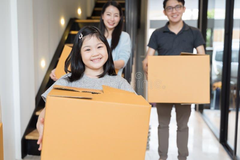 Портрет счастливой азиатской семьи двигая к новому дому с картонными коробками стоковая фотография rf