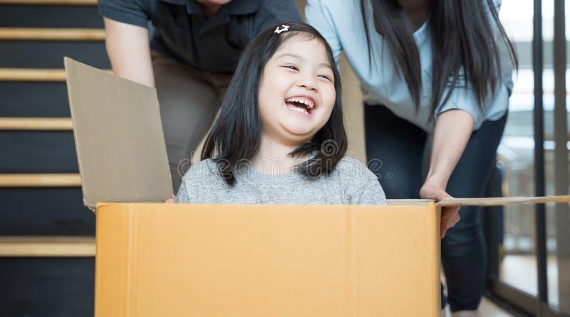Портрет счастливой азиатской семьи двигая к новому дому с картонными коробками и играя картонную коробку стоковые фото