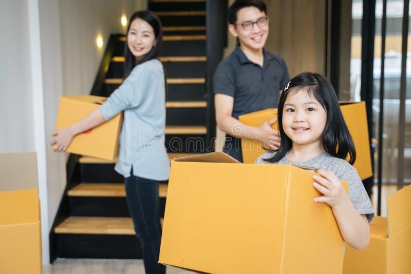 Портрет счастливой азиатской семьи двигая к новому дому с картонными коробками стоковые изображения