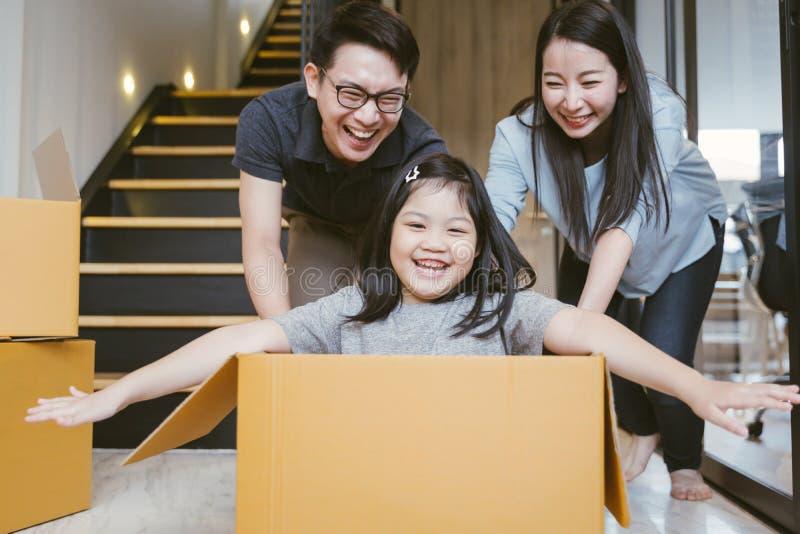 Портрет счастливой азиатской семьи двигая к новому дому с картонными коробками стоковое изображение rf