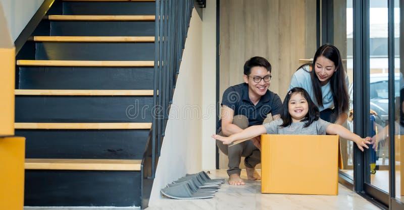Портрет счастливой азиатской семьи двигая к новому дому с картонными коробками и играя картонную коробку стоковое изображение rf