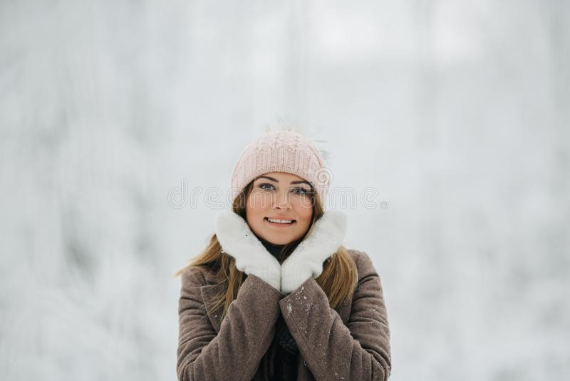 Портрет счастливой белокурой женщины в шляпе на прогулке в лесе зимы стоковое изображение