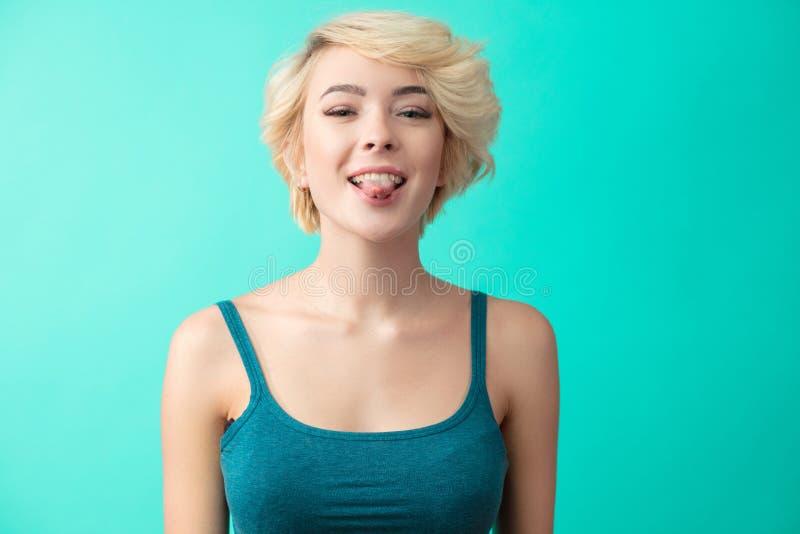 Портрет счастливой белокурой женщины с языком вставляя вне смотреть стоковая фотография